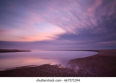 Time exposure of Siltcoos River meeting Pacific Ocean and moving clouds at sunset creates a beautiful graphic image
