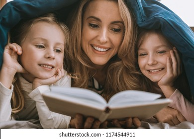 Time for fairytales. Delighted nice woman holding a book while resign fairytales to her daughters