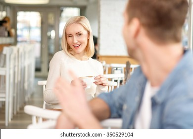 Time to flirt. Beautiful smiling young woman drinking coffee in the cafe and winking at handsome man while flirting with him