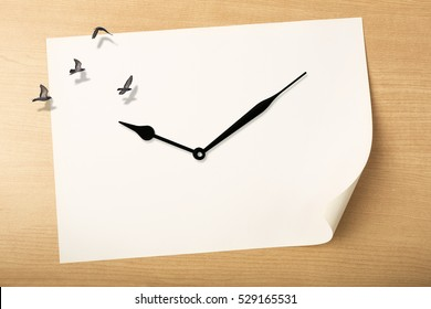 Time fly concept, Time to relax concept, clock with birds flying above white paper on wood background