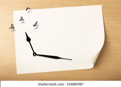 Time fly concept, Relaxing time concept, clock with birds flying above white paper on wood background