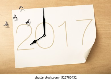 Time fly to new year 2017 concept, clock with birds flying above white paper on 2017 and  wood background