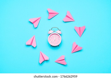 Time flying concept with pink paper airplanes and alarm clock on a blue background. Last-minute trip. Passage of time notion. Time to travel symbol.