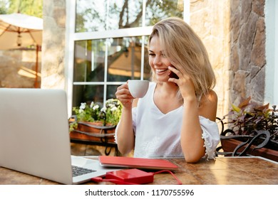 Time for freelance busines. Amazing charming young businesswoman, drinking a coffee, while having a phone conversation and working on laptop, woman resting at the cafe table. Break time for freelancer
