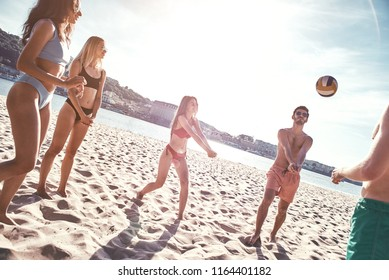 Time with friends. Group of young people playing volleyball on the beach