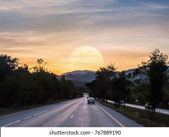 Its time to go back to our rest area or home. The giant moon of supermoon phenomenon is appeared behind mountain of the highway in Chiangmai, Thailand.