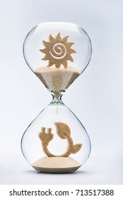 Time for green energy concept with falling sand taking the shape of an electric cord and leaf inside a hourglass