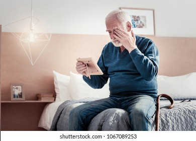 Time for grieving. Cheerless depressed aged man looking at the photo and crying while missing his wife