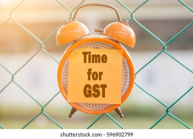 TIME FOR  GST  Season finance concept.orange analog clock hanging on the fence over blurry background