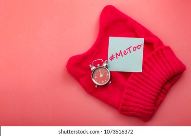 Time is up and hashtag metoo concept with a post it note, a clock and a pussyhat on a pink background with copy space. metoo is the movement that raises awareness about sexual assault and discriminati
