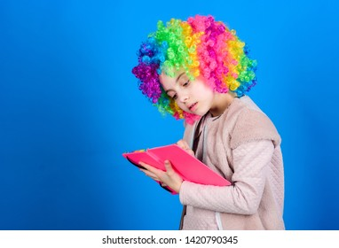 Time to have fun. Circus school. Study hard. Ridiculous story. Reading funny book. Literature club. Jokes book concept. Kid colorful curly wig artificial hair clown style hold book. Reading jokes.
