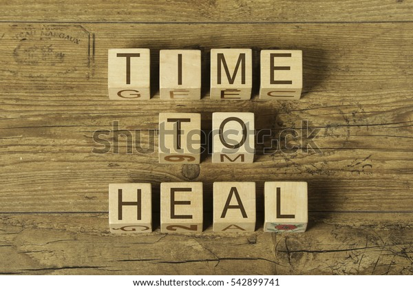 time to heal text on cubes on wooden backgound