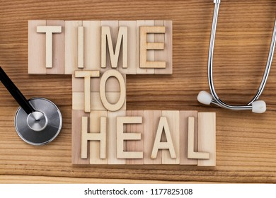time to heal-  text in vintage letters on wooden blocks with stethoscope . Medicine concept.