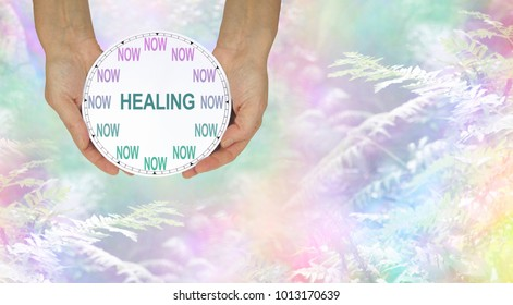 The time for healing is NOW - female hands holding a clock with no hands that has NOW in place of the numerals and HEALING instead of hands against a rainbow colored woods and fern background