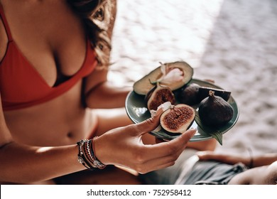 Time for healthy snack! Close-up of young woman holding a plate with fig and avocado while resting with her boyfriend on the beach