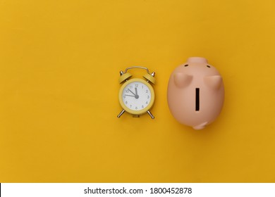 Time to invest. Piggy bank, alarm clock on yellow background. Top view. Flat lay