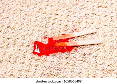 A time lapse of a melting popsicle on white carpet shows the icy treat melt into a sticky juice and absorb right into the carpet.