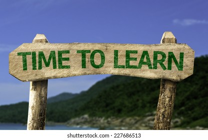 Time To Learn wooden sign with a beach on background