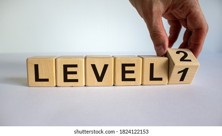 Time for Level 2. Hand is turning a cube and changes the word 'level 1' to 'level 2'. Beautiful white background. Business concept. Copy space.