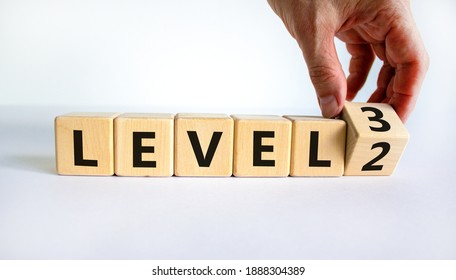 Time for Level 3. Hand turns a cube and changes words 'level 2' to 'level 3'. Beautiful white background. Business and next level concept. Copy space.