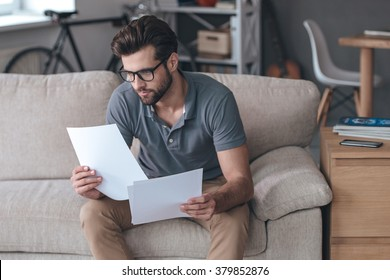 Time to look through bills. Handsome young man holding papers and looking at it while sitting on the couch at home
