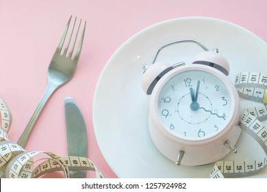 Time to lose weight , eating control or time to diet concept , alarm clock with healthy tool concept decoration on pink background