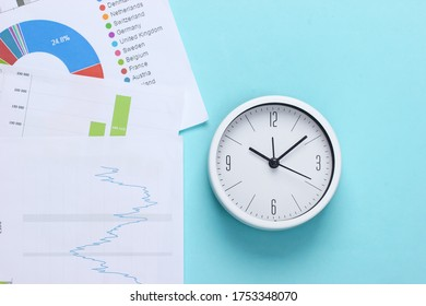 Time to make money, invest. Graphs and charts, clock on a blue background. Business concept. Top view