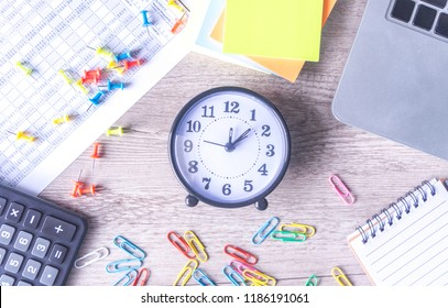 Time management concept. Composition with alarm clock on wooden table with laptop computer, stationary and calculator, top view above
