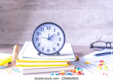 Time management concept. Composition with alarm clock on wooden table with stationary, glasses and calculator