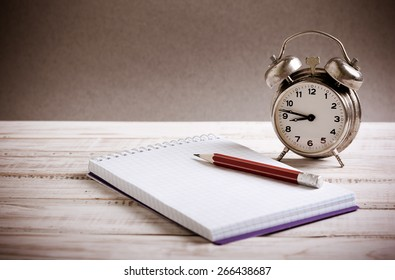 Time management concept: vintage alarm clock, pencil and notepad