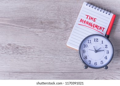 Time management hand written on paper notebook with clock lay on brown wooden desk, top view