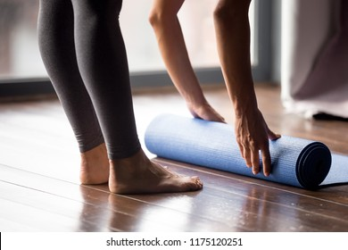 Time for meditation, fitness session, well-being concept. Girl wearing grey sporty pants rolling fitness mat before, after class in yoga studio club or at home on wooden floor. Hands and legs close up