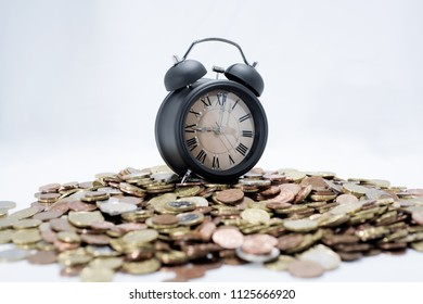 Time and money abstraction. A lot of coins with elegant black clock.