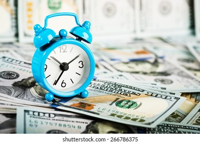 Time is money. Alarm clock and dollar banknotes.