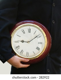 Time is money: Business man holding clock
