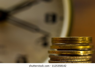 Time is money! Close-up of stacked coins and an alarm clock. The clock's face is in the background.