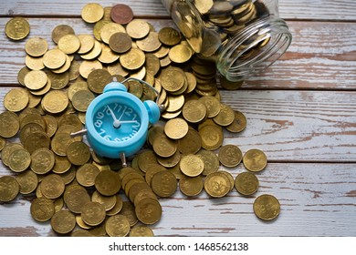 Time is money concept, close up coins in glass jar and scattered on wooden table with fallen clock.
