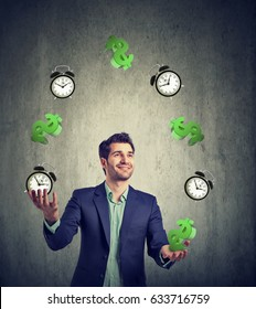 Time is money concept. Happy young businessman juggling dollar signs and alarm clock
