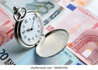 Time is money concept with pocket watch and euros bills closeup