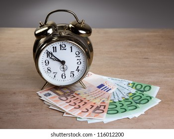Time is Money concept shot with old mechanical Alarm Clock and Euro Banknotes
