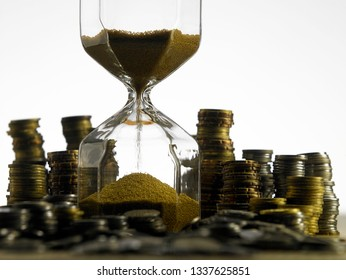 Time is money concept Stack of coins with hourglass on wood table