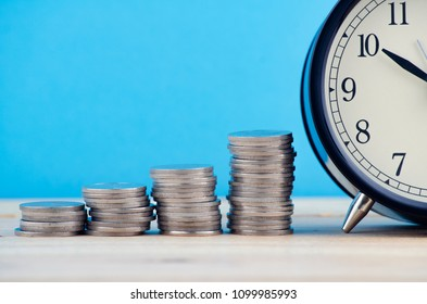Time is Money concept, stacking coins and alarm clock on wooden desk