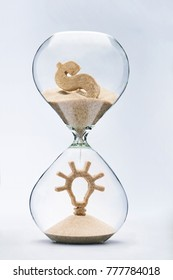 Time and money is creativity concept. Light bulb made out of falling sand from dollar symbol flowing through hourglass.
