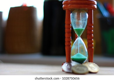 Time is money, don't waste it, make it worth it. An hourglass with falling sand and coins at its feet to underline the importance and value of time.