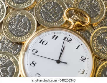 Time and money, gold watch near midnight on a pile of coins