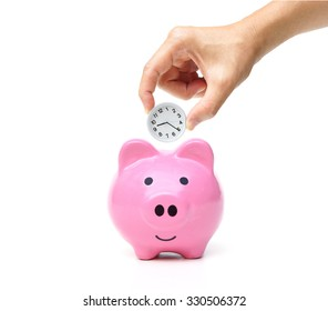 Time and money - hand putting a clock into a pink piggy bank