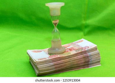 """Time is money. Hourglass and Russian banknotes. Translation: """"The ticket of the bank of Russia, five thousand rubles"""""""