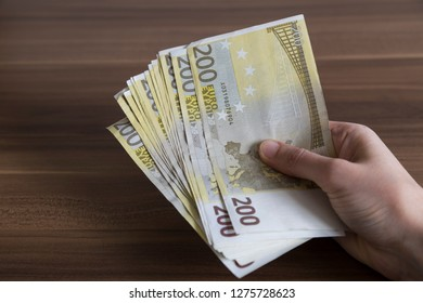 time to money investment for financial concept and bank. Euro and hand on the wooden background.