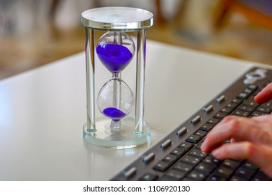 Time is money, make money and time management business and technology concept, hourglass on laptop keyboard macro view. deadline idea, symbol, concept