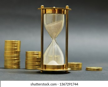 Time is money. Stacks of golden coins against an hour glass.  Time and tide wait for no man, concept.